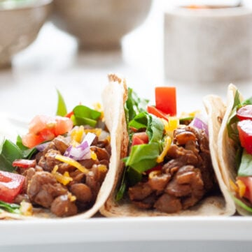 a plate of 3 instant pot lentil tacos with bowls in the background