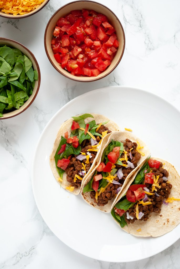 A top down view photo of a plate of lentil tacos with bowls of chopped tomato and spinach to the side of it.