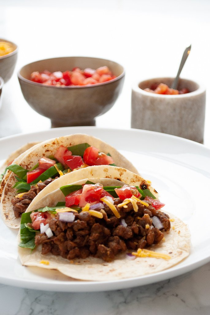 A plate of three instant pot lentil tacos with toppings in the background.