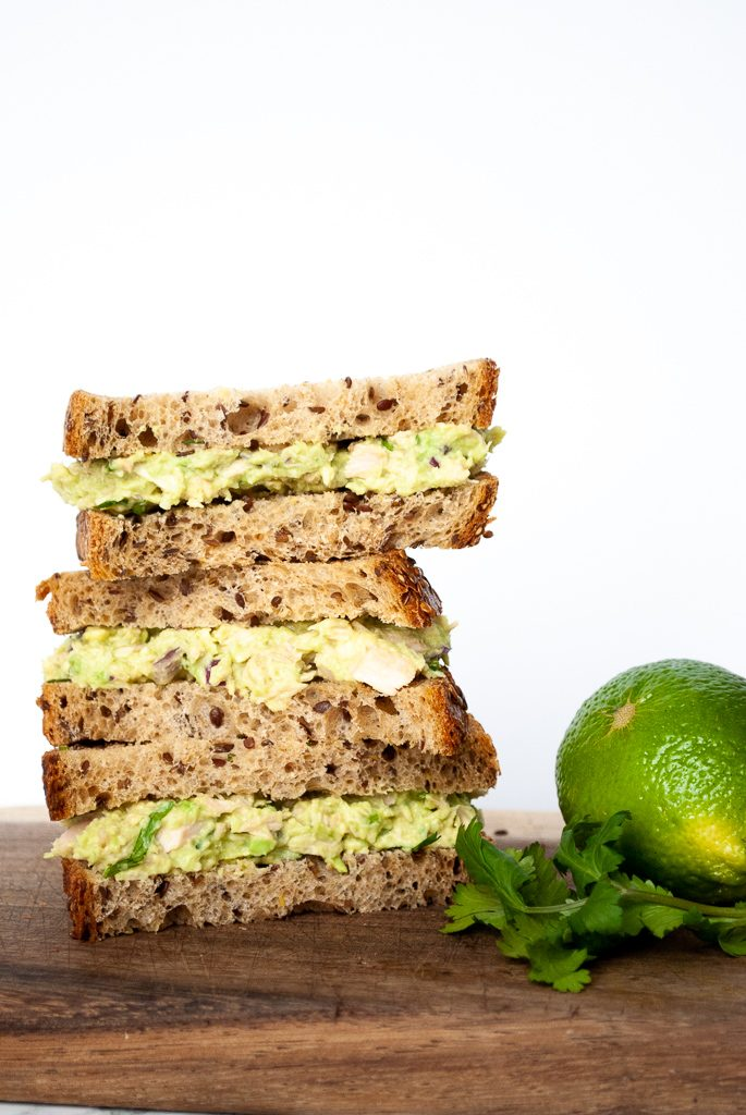 a stack of tuna sandwiches made with avocado instead of mayo on a cutiting board next to a sprig of cilantro and a lime