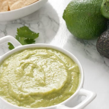 a bowl of avocado salsa verde with tortillas chips, a lime, and avocado in the background