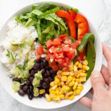a hand holding a black bean burrito bowl