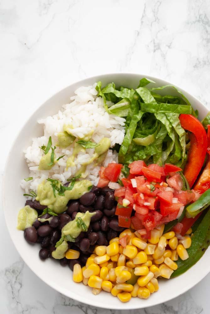 A burrito bowl with black beans, rice, corn, sautéed peppers, lettuce, pico de gallo and avocado salsa verde.