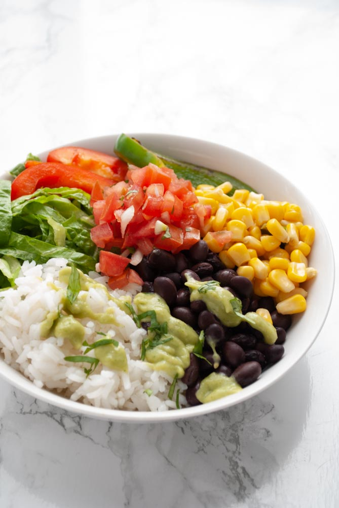 a black bean burrito bowl topped with avocado salsa and pico de gallo