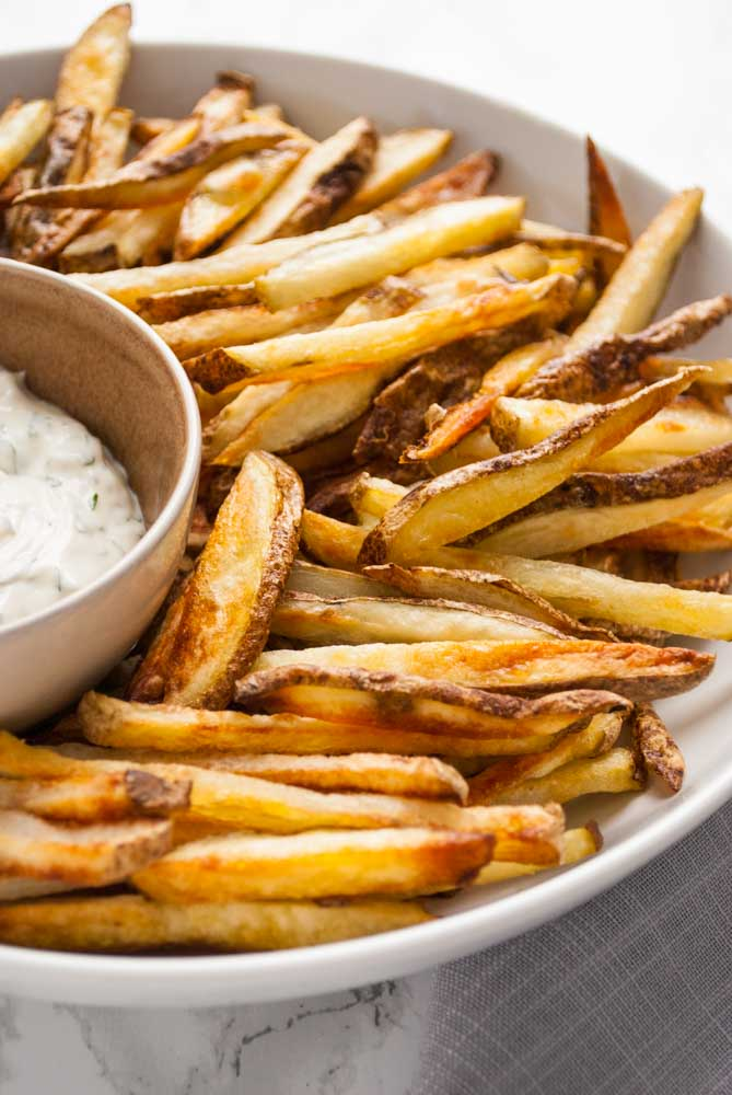 A plate of crispy oven fries on a plate with a bowl of dip.