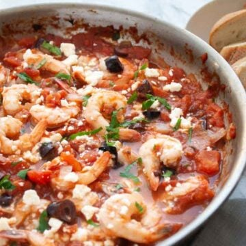 a pan filled with greek style shrimp cooked in tomatoes with feta cheese
