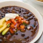 a bowl of black bean soup topped with avocado, sour cream and pico de gallo