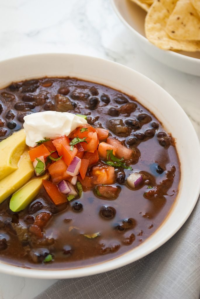 a bowl of black bean soup topped with avocado, sour cream and pico de gallo