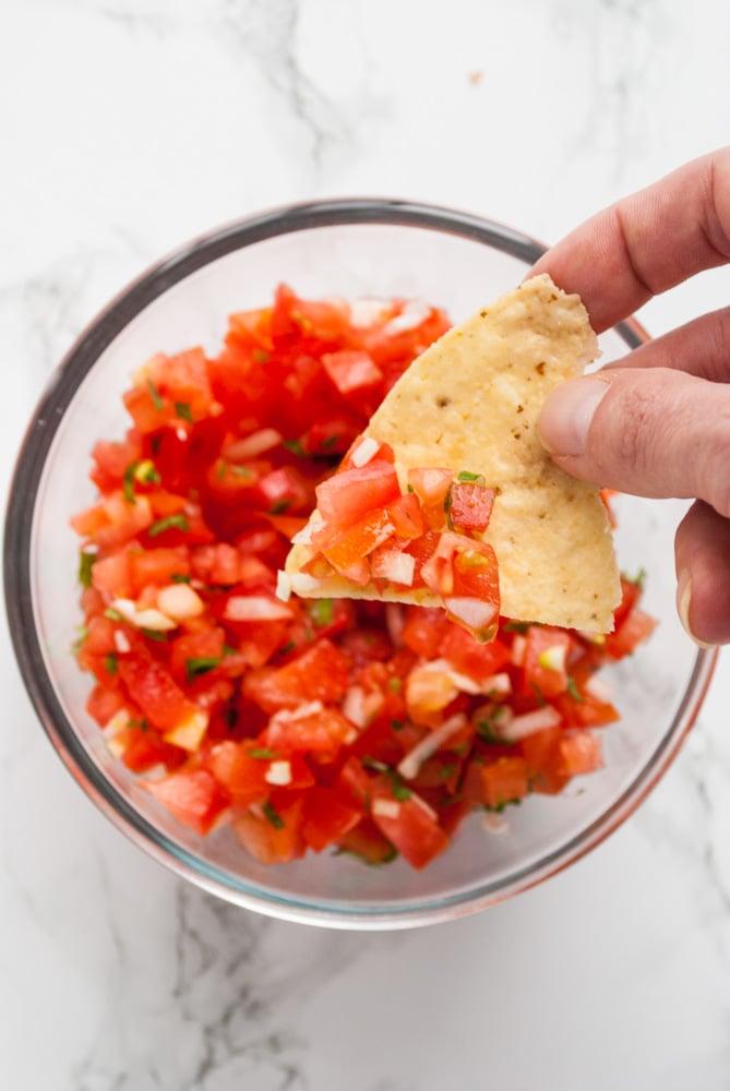 a person dipping a tortilla chip into a bowl fresh homemade pico de gallo