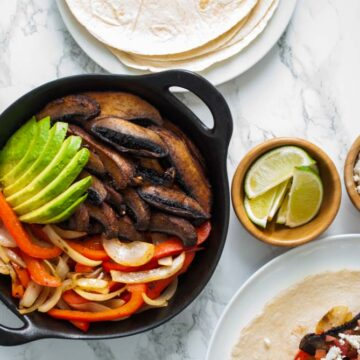 A table topped with a skillet of portobello fajitas, flour tortillas, and other fajita toppings.