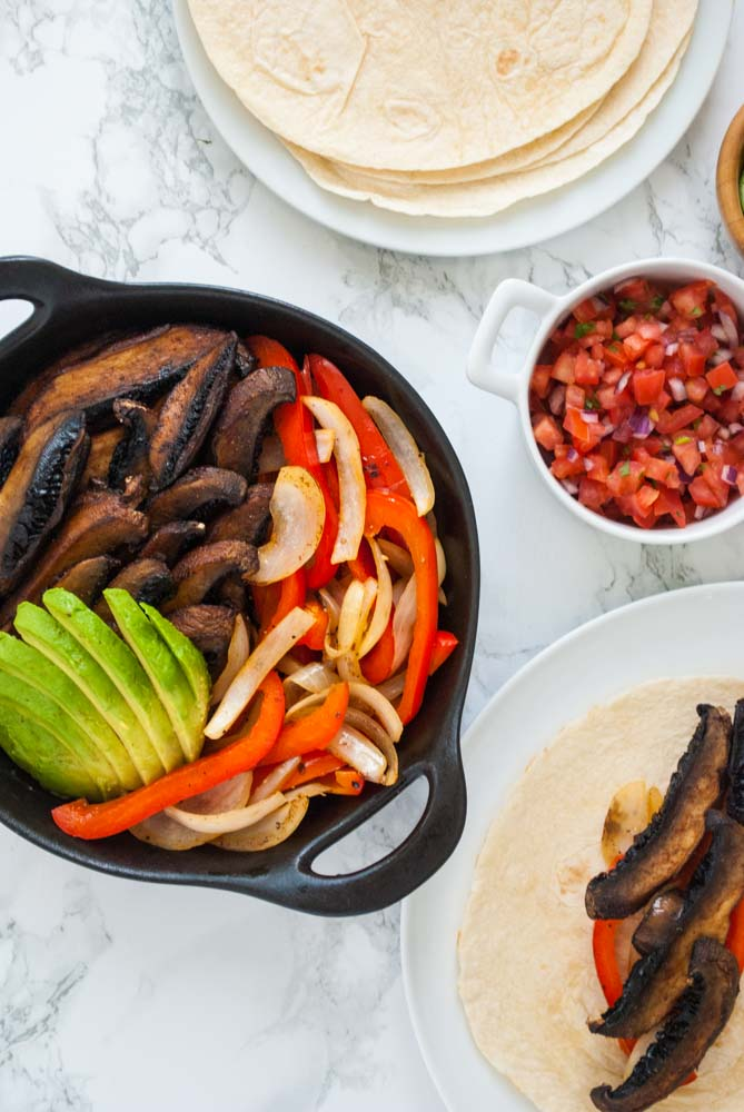 A table set with a skillet of portobello mushroom fajitas along with toppings and tortillas.
