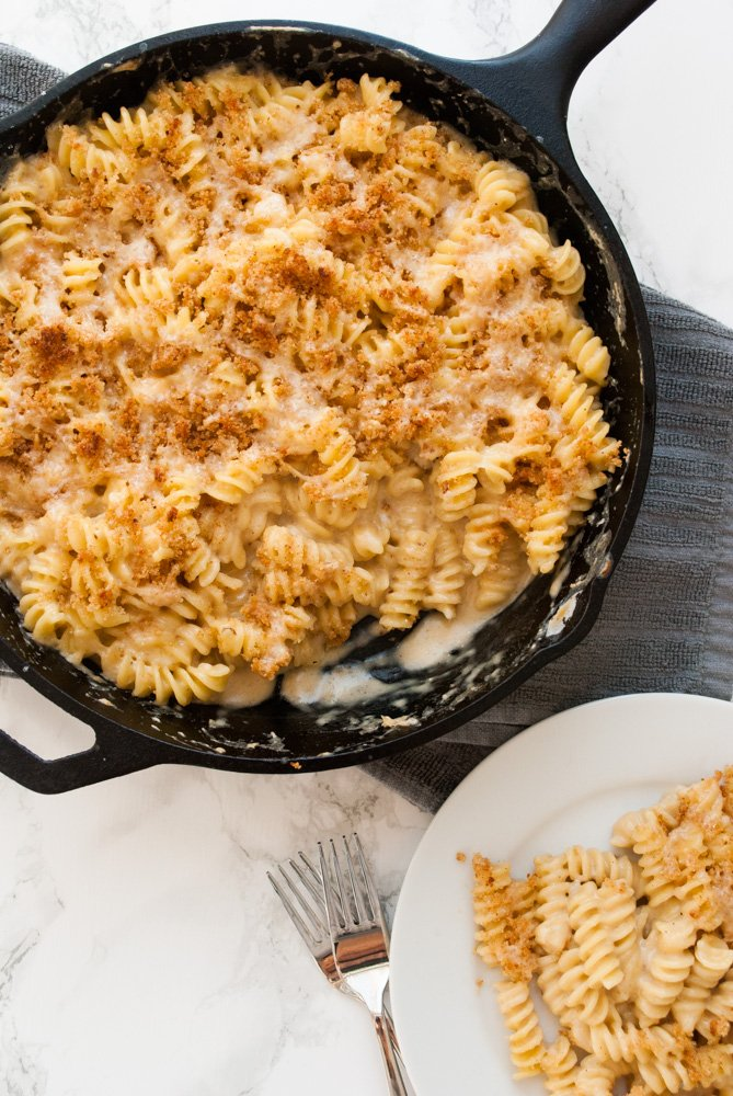 a cast iron skillet filled with mac and cheese on a table ready to be served