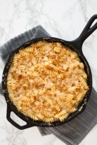 a skillet with freshly cooked mac and cheese resting on a kitchen towel
