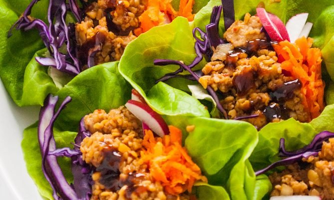 a plate containing vegetarian tempeh lettuce wraps with shredded carrot and red cabbage toppings