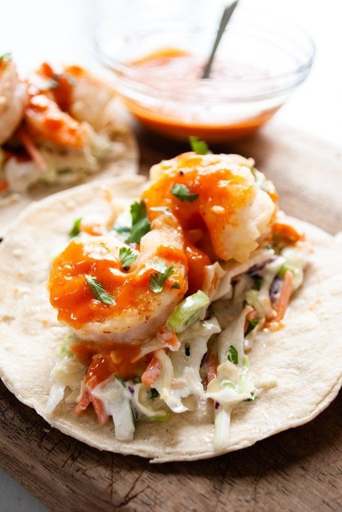 a close up shot of a shrimp taco with bang bang sauce