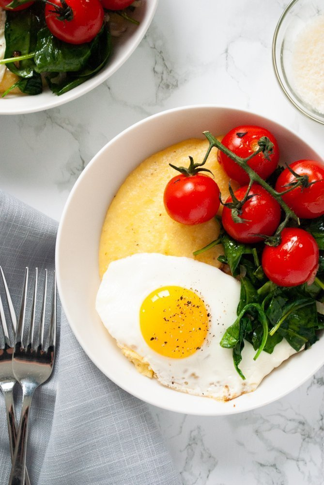 a table with breakfast polenta bowls, a bowl of grated parmesan and cutlery on it