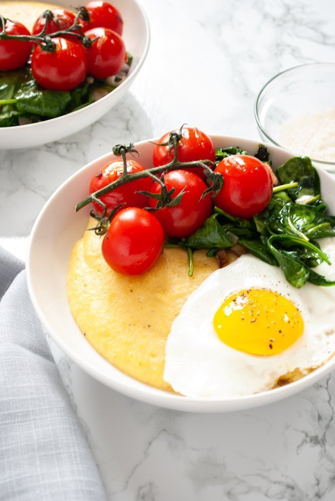 a side angle photo of a breakfast polenta with a second bowl in the background