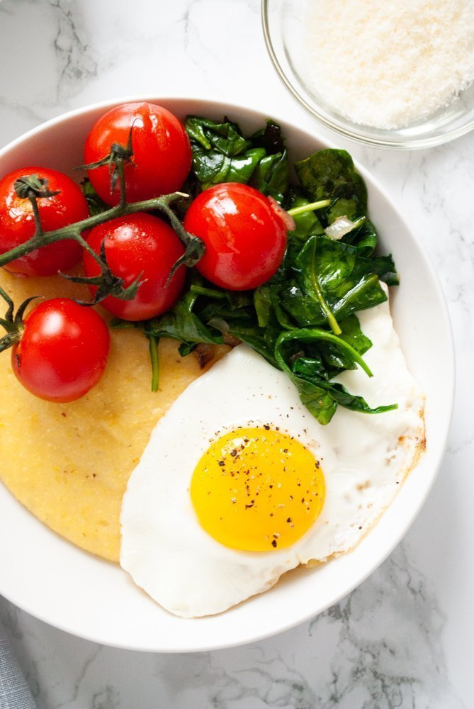 a bowl of breakfast polenta with spinach, cherry tomatoes and fried egg on a table next to a bowl of grated parmesan