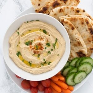 a bowl of chana dal hummus surrounded by veggies and pita