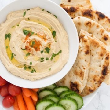 A serving tray with creamy hummus surrounded by pita bread, cucumber, carrots and cherry tomatoes.