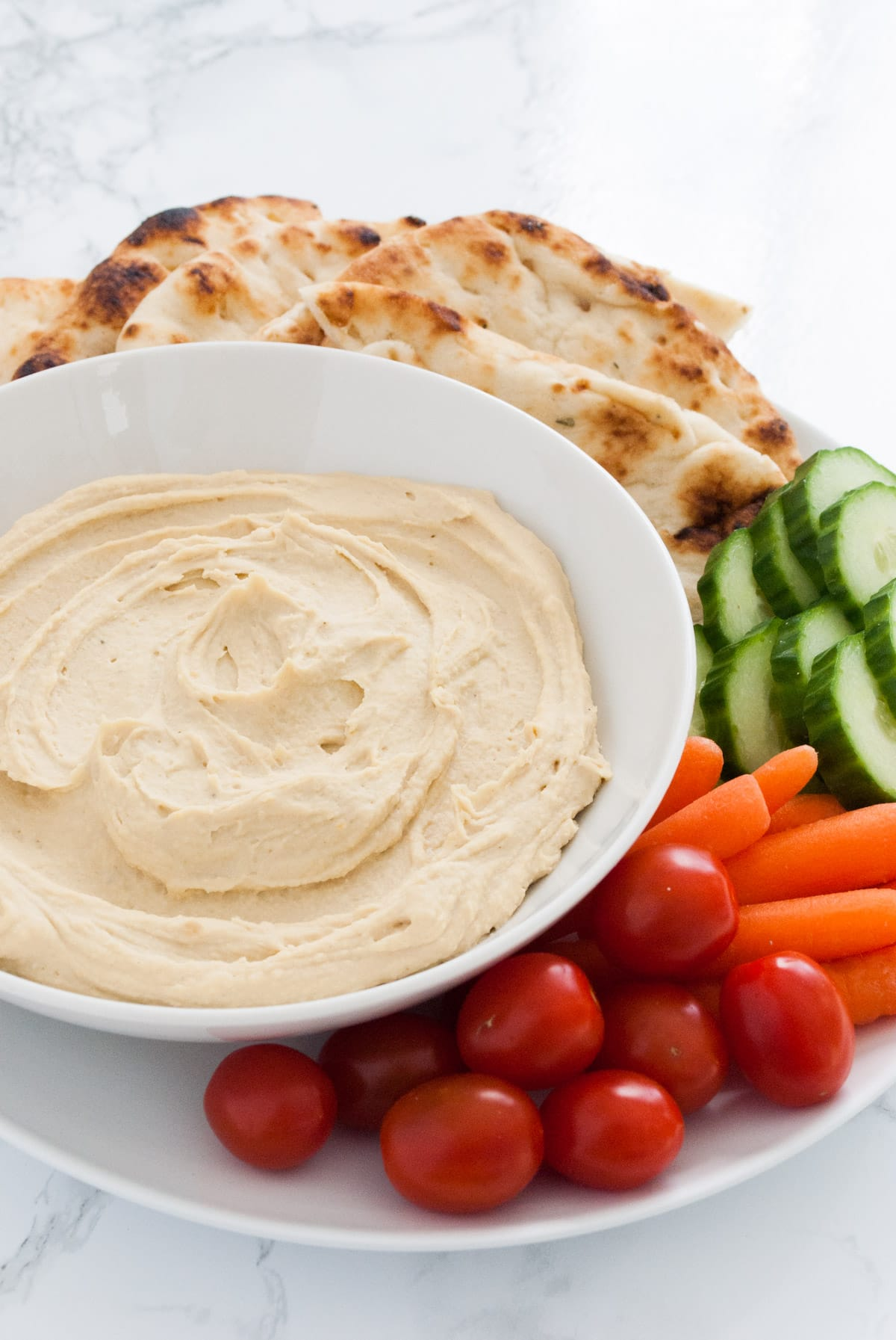 Creamy hummus in a bowl surrounded by pita bread and cut veggies.