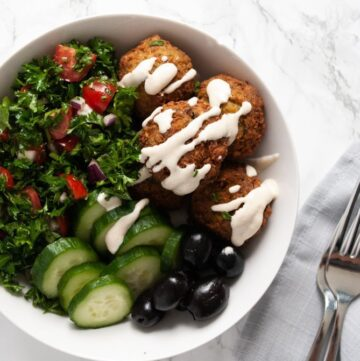 a falafel bowl on a table next to a napkin and cutlery