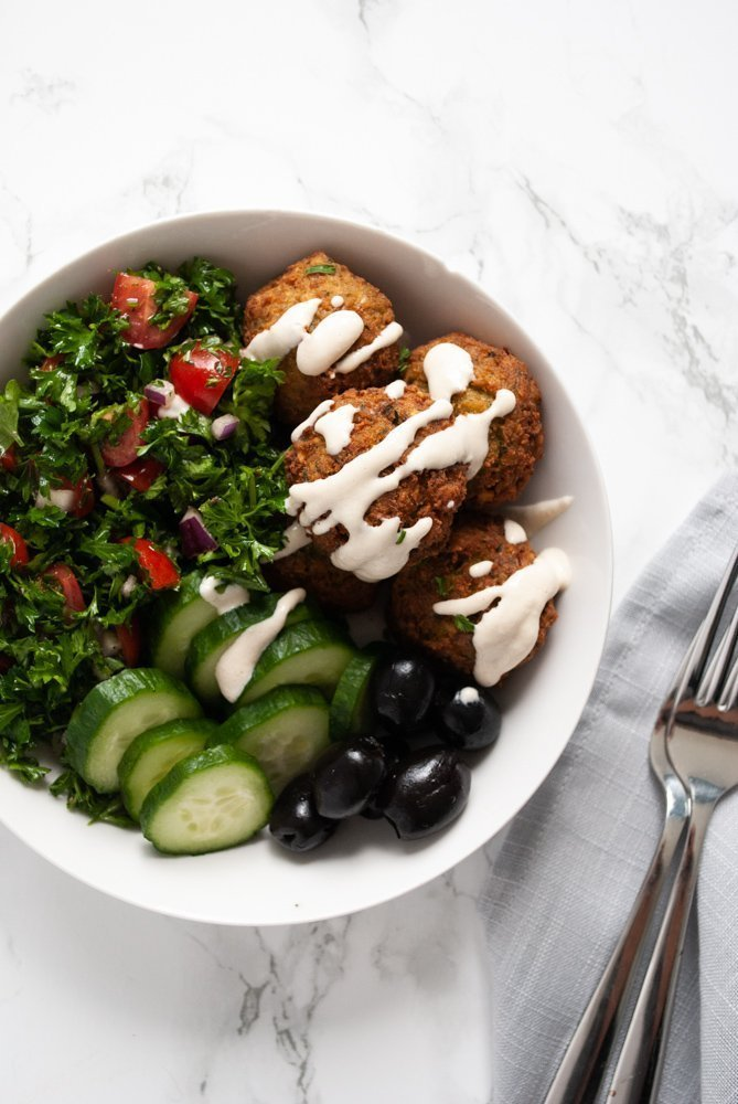 A bowl of homemade falafel, parsley tomato salad, cucumber, black olives and tahini sauce