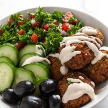 a bowl of homeamde falafel, parsley tomato salad, cucumber, black olives and tahini sauce