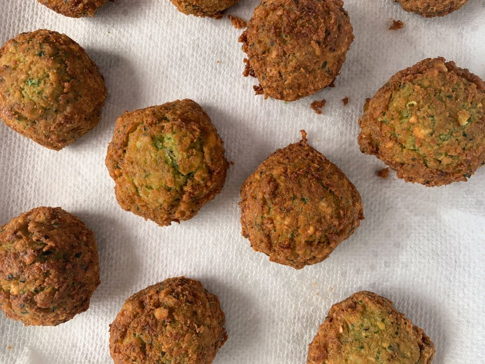 fully cooked falafel balls resting on paper towel after being fried.
