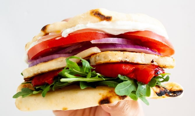 a hand holding up a fried halloumi sandwich with roasted red peppers, tomato, onion and tzatziki.