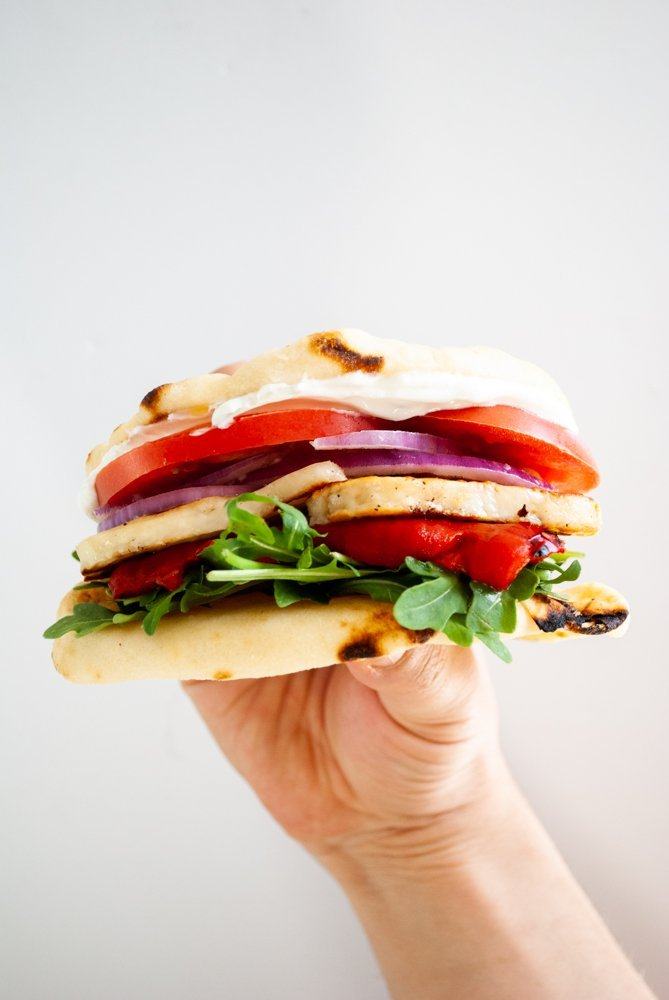 a hand holding a sandwich of fried halloumi with roasted red pepper, arugula, tomato, red onion and tzatziki