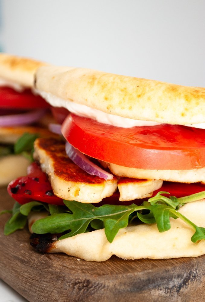 a side view of a halloumi sandwich on a cutting board