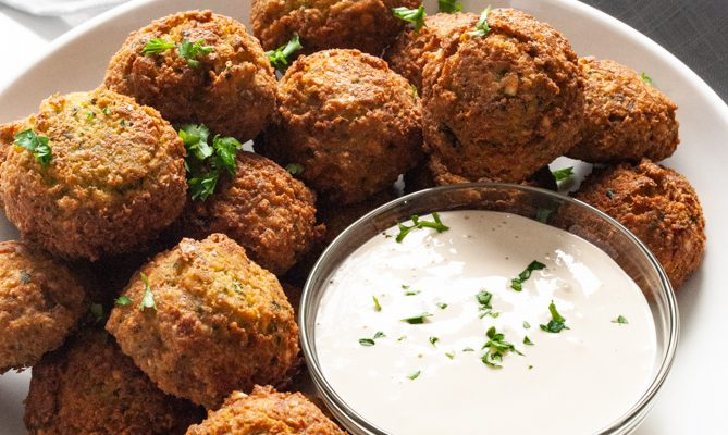 a bowl of falafel balls next to tahini sauce