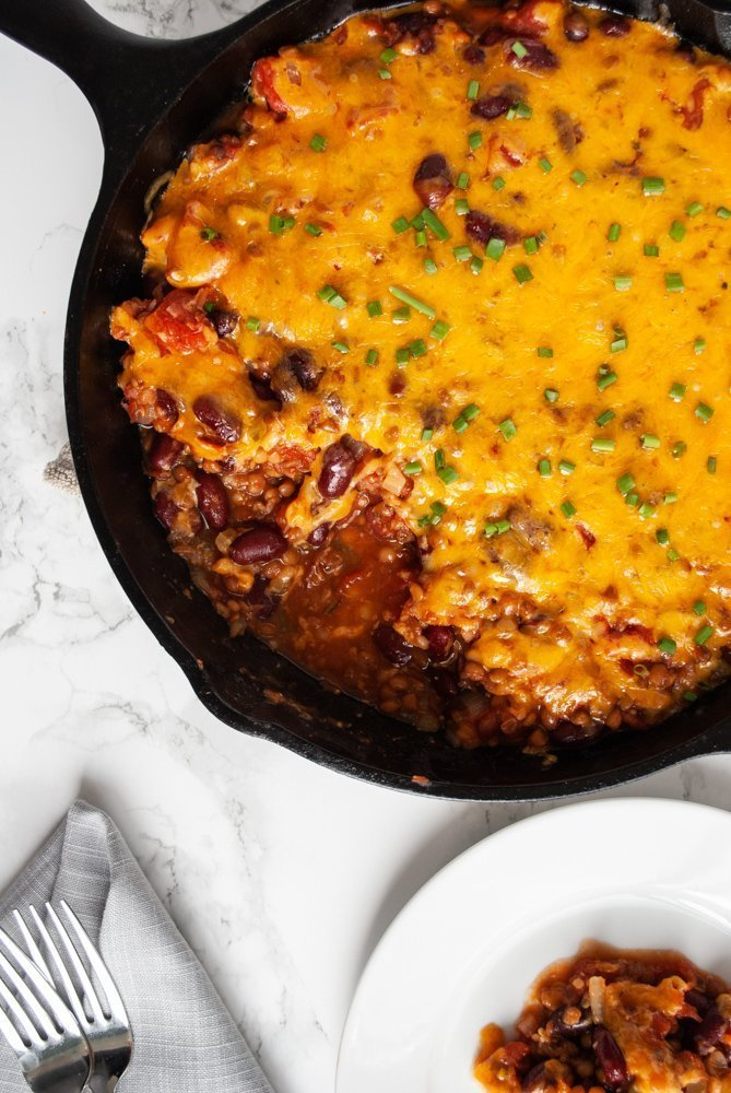 A top view of a skillet filled with lentil casserole topped with melted cheese.