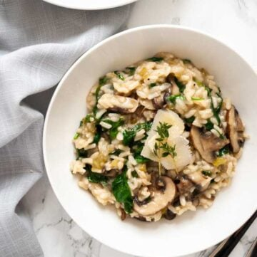 a bowl of mushroom and spinach risotto on a table next to a napkin and cutlery