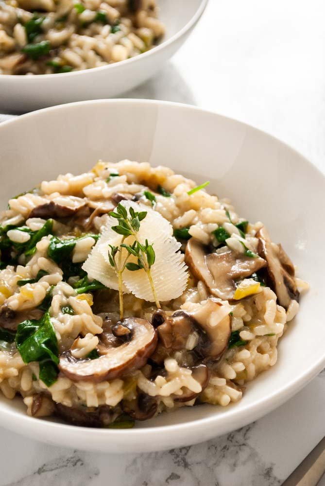 a bowl of spinach and mushroom risotto topped with a sliver of parmesan cheese and thyme sprigs