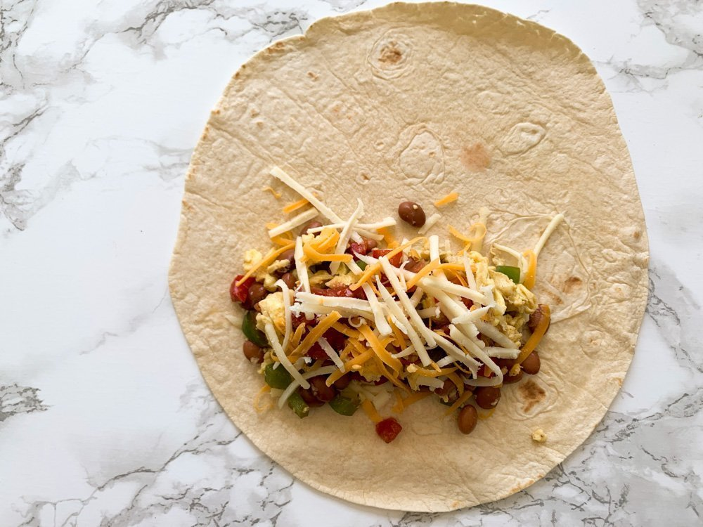 a tortilla spread out with breakfast burrito fillings waiting to be folded