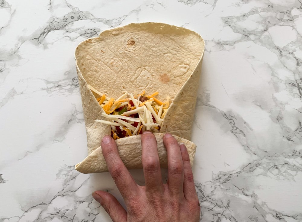 a breakfast burrito mid roll with the bottom and sides turned in