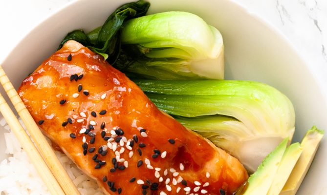 a bowl filled with teriyaki salmon, rice, avocado and bok choy.