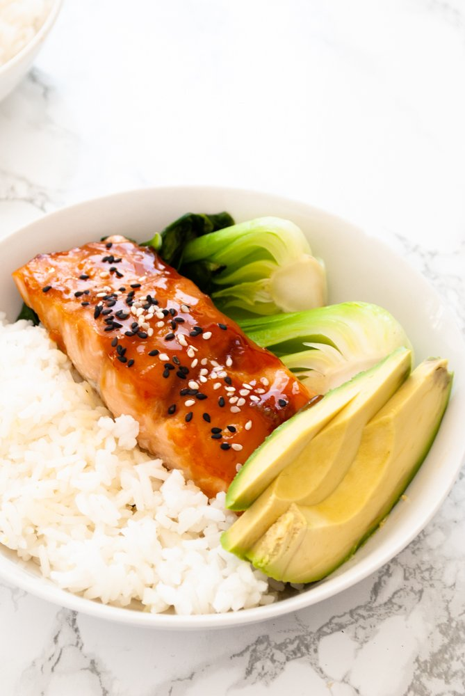 a bowl with rice, teriyaki glazed salmon, stir-fried bok choy and avocado slices