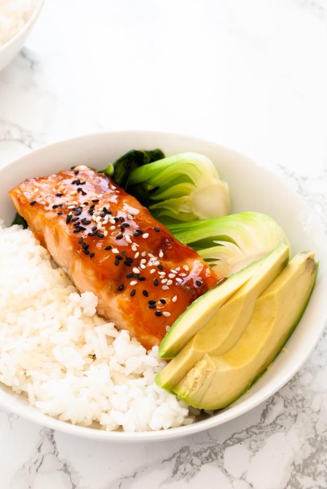 A bowl with rice, teriyaki glazed salmon, stir-fried bok choy and avocado slices.