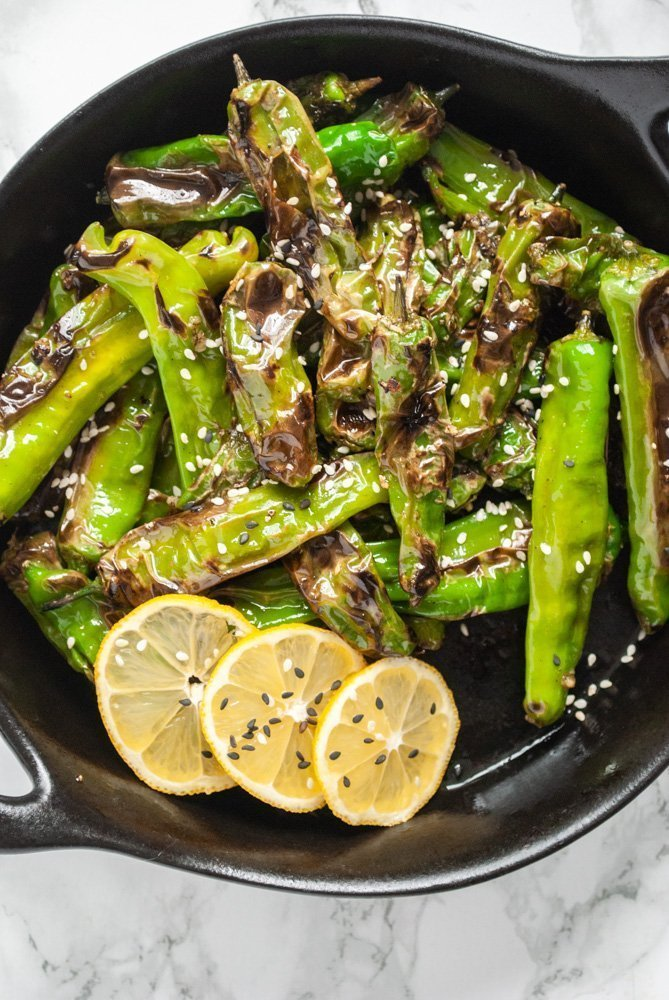 blistered shishito peppers in a dish with slices of lemons