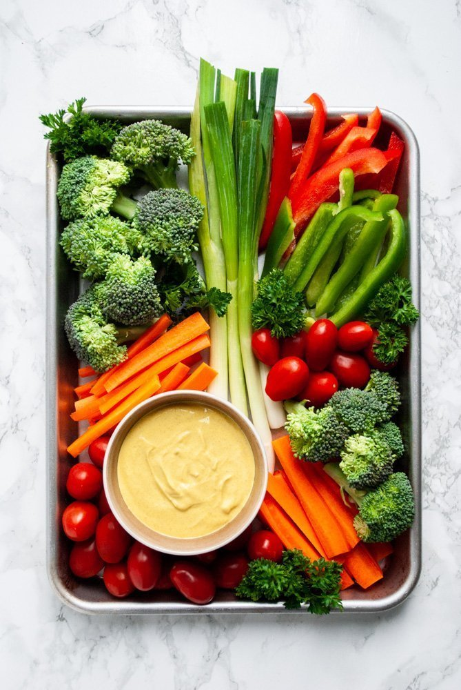 mixed vegetables on a tray with a bowl of curry dip