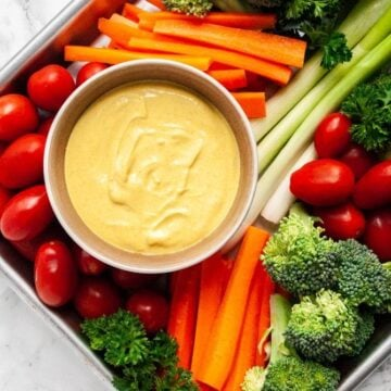 a tray filled with crudite and a bowl of curry dip