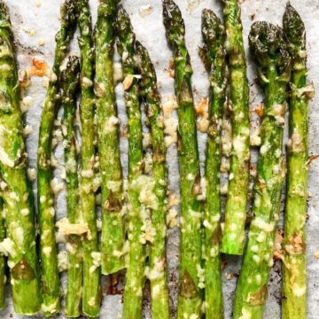 a close up shot of freshly roasted garlic parmesan asparagus