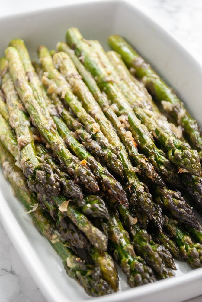 A serving dish with garlic parmesan roasted asparagus.