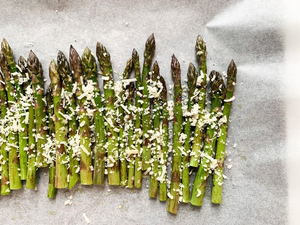 Asparagus spears covered with oil, garlic and parmesan cheese on a baking sheet.