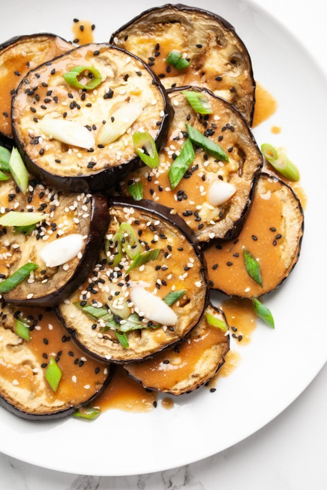 roasted eggplant rounds drizzled with miso sauce and garnished with green onions and sesame seeds