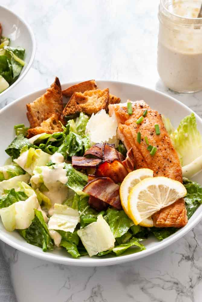 a bowl of salmon Caesar salad next to a jar of homemade caesar salad dressing