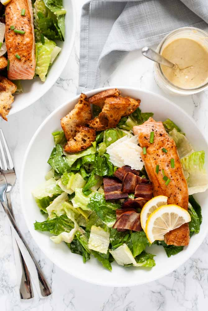 a couple of bowls of salmon caesar salad on a table
